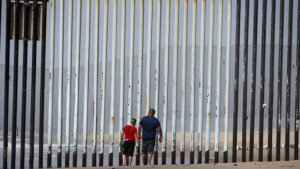 "Two people walk towards metal bars marking the United States border where it meets the Pacific Ocean Wednesday, March 2, 2016, in Tijuana, Mexico. Former Mexican President Vicente Fox on Wednesday stood by his comparison of Donald Trump to Adolf Hitler, saying the Republican presidential front-runner ""believes in the white supremacy."" Fox is calling on Americans to ""wake up"" from ""this Republican nightmare."" He made the remarks Wednesday in an interview taped for Fox News Channel's ""Hannity."" Trump has angered many Mexicans for his campaign rhetoric denigrating some immigrants as ""rapists"" who bring crime and drugs to the United States, and his promise to build a wall along the entire US-Mexico border. (AP Photo/Gregory Bull)"