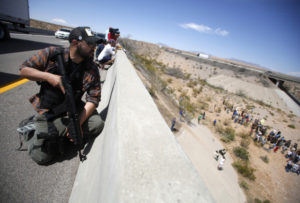 Eric Parker from central Idaho stands watch on a bridge with his weapon as protesters gather by the Bureau of Land Management's base camp, where cattle that were seized from rancher Cliven Bundy are being held, near Bunkerville, Nevada.
